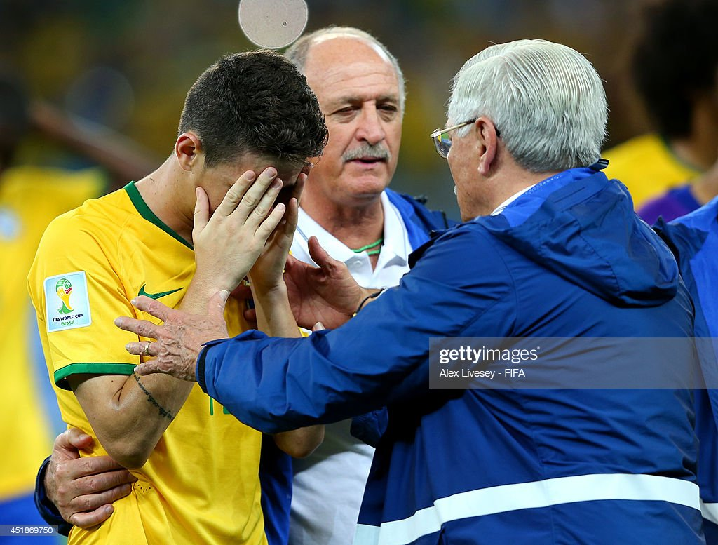 Oscar of Brazil is consoled by a team staff after the 1-7 defeat in the 2014 FIFA World Cup Brazil Semi Final match between Brazil and Germany at Estadio Mineirao on July 8, 2014 in Belo Horizonte, Brazil.