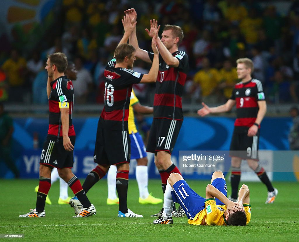 Oscar of Brazil reacts on the pitch as Germany celebrate their 71 win during the 2014 FIFA World Cup Brazil Semi Final match between Brazil and...