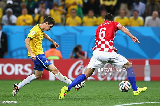 Oscar of Brazil shoots and scores against Dejan Lovren of Croatia in the second half during the 2014 FIFA World Cup Brazil Group A match between...