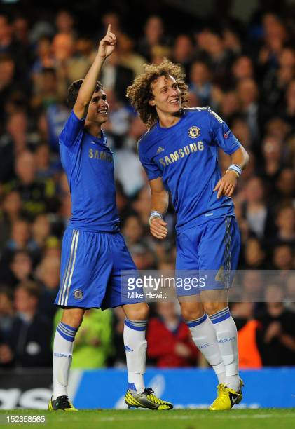 Oscar of Chelsea celebrates scoring their first goal with David Luiz of Chelsea during the UEFA Champions League Group E match between Chelsea and...