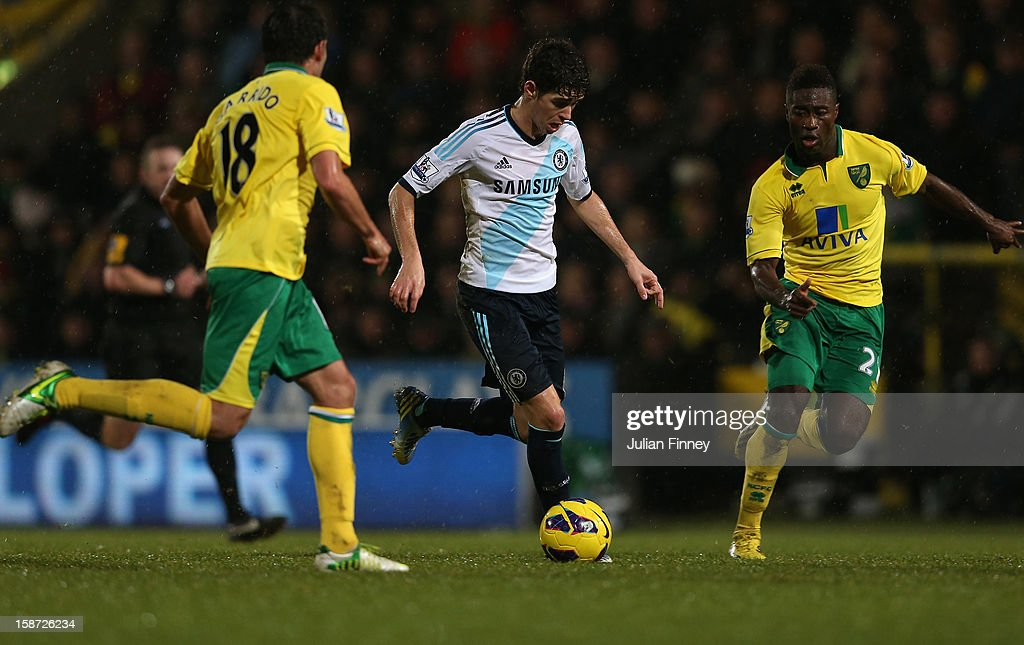 Oscar of Chelsea goes past Javier Garrido of Norwich City and Alexander Tettey of Norwich during the Barclays Premier League match between Norwich City and Chelsea at Carrow Road on December 26, 2012 in Norwich, England.