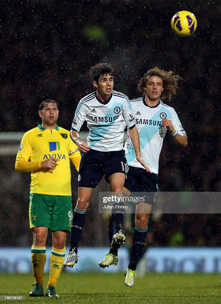 Oscar of Chelsea heads the ball as David Luiz of Chelsea and Grant Holt of Norwich City look on during the Barclays Premier League match between Norwich City and Chelsea at Carrow Road on December 26, 2012 in Norwich, England.