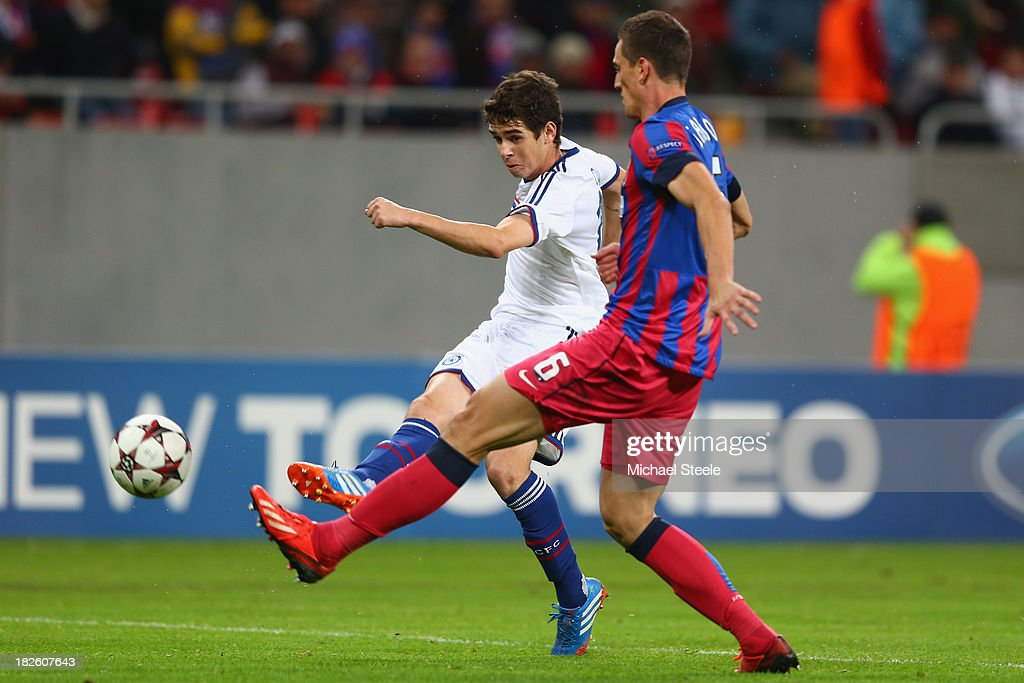 Oscar (L) of Chelsea shoots as Florin Gardos (R) of Steaua Bucuresti closes in during the UEFA Champions League Group E Match between FC Steaua Bucuresti and Chelsea at the National Arena Stadium on October 1, 2013 in Bucharest, Romania.