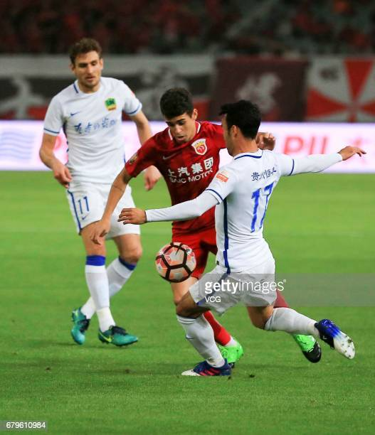 Oscar of Shanghai SIPG and Ilhamjan Iminjan of Guizhou Hengfeng compete for the ball during the eighth round match of 2017 Chinese Football...
