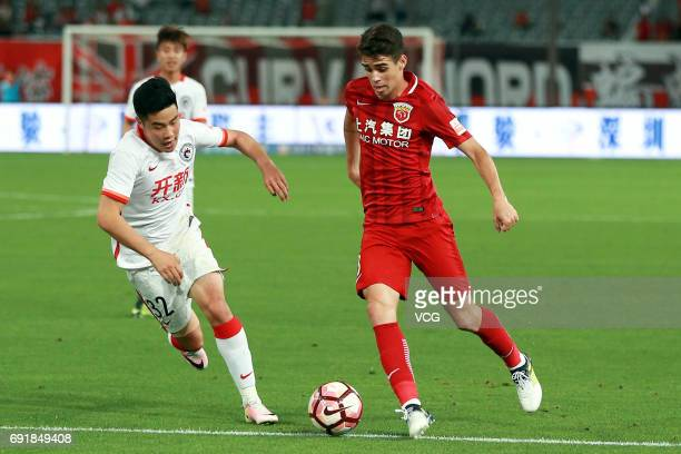 Oscar of Shanghai SIPG and Ni Yusong of Liaoning Whowin compete for the ball during the 12th round match of 2017 Chinese Football Association Super...