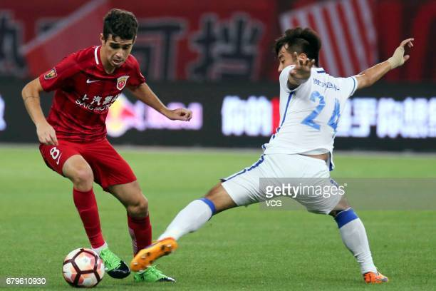 Oscar of Shanghai SIPG and Wang Jun of Guizhou Hengfeng compete for the ball during the eighth round match of 2017 Chinese Football Association Super...