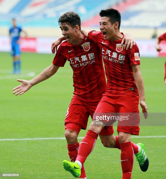 Oscar of Shanghai SIPG celebrates with team mate Wu Lei after scoring a goal during the 10th round match of CSL Chinese Football Association between...