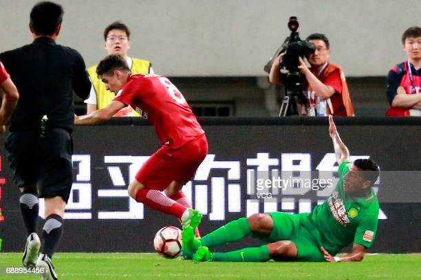Oscar of Shanghai SIPG competes for the ball with Ralf of Beijing Guoan during the 11th round match of 2017 Chinese Football Association Super League...