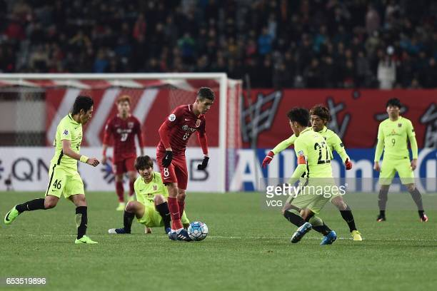 Oscar of Shanghai SIPG is challenged by Urawa Red Diamonds players during the AFC Champions League Group F match between Shanghai SIPG and Urawa Red...