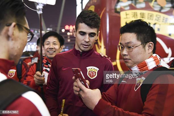 Oscar of Shanghai SIPG poses for photos with fans at Pudong International Airport prior to his team's departure to the Doha training camp on January...