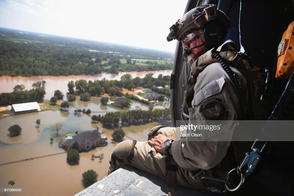 Oscar Peru of U.S. Customs and Border Protection searches for flood victims from a helicopter after torrential rains pounded the area following Hurricane and Tropical Storm Harvey on August 31, 2017 near Sugar Land, Texas. Harvey, which made landfall north of Corpus Christi August 25, has dumped nearly 50 inches of rain in and around areas Houston.