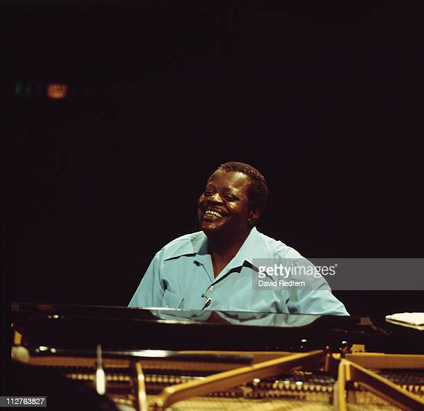 Oscar Peterson Canadian jazz pianist smiling as he sits behind a piano circa 1980