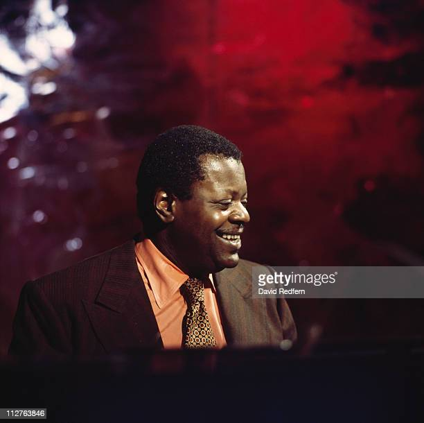 Oscar Peterson Canadian jazz pianist smiling as he sits behind a piano circa 1975