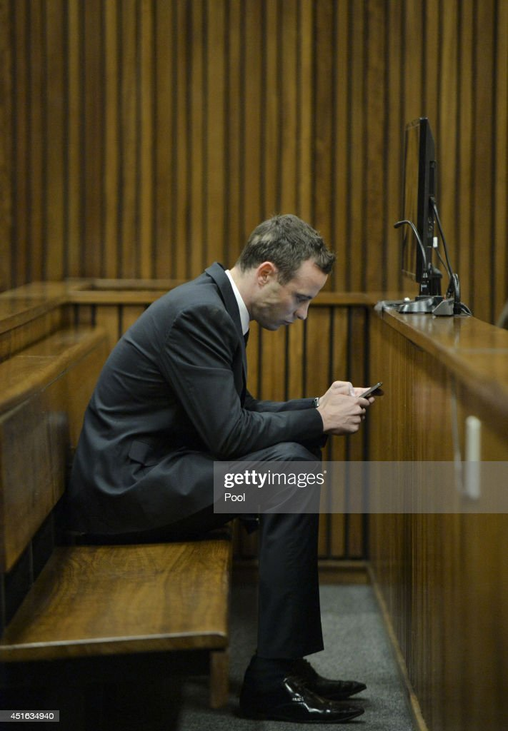 Oscar Pistorius checks his phone in the Pretoria High Court on July 3, 2014, in Pretoria, South Africa. Oscar Pistorius stands accused of the murder of his girlfriend, Reeva Steenkamp, on February 14, 2013. This is Pistorius' official trial, the result of which will determine the paralympian athlete's fate.