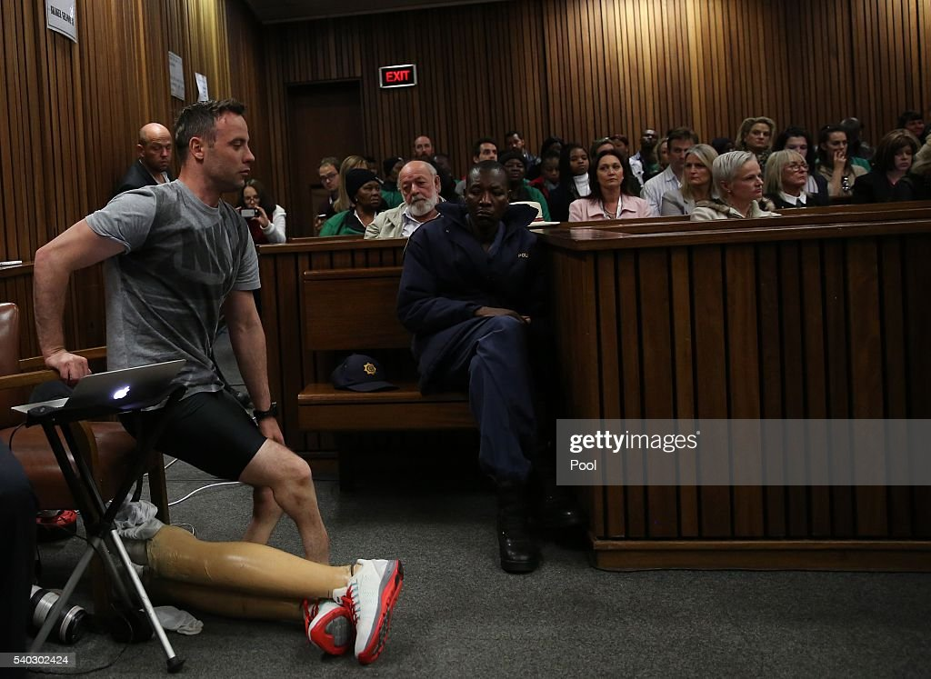Oscar Pistorius takes off his legs as he prepares to walk across the courtroom without his prosthetic legs during the third day of Oscar's hearing...