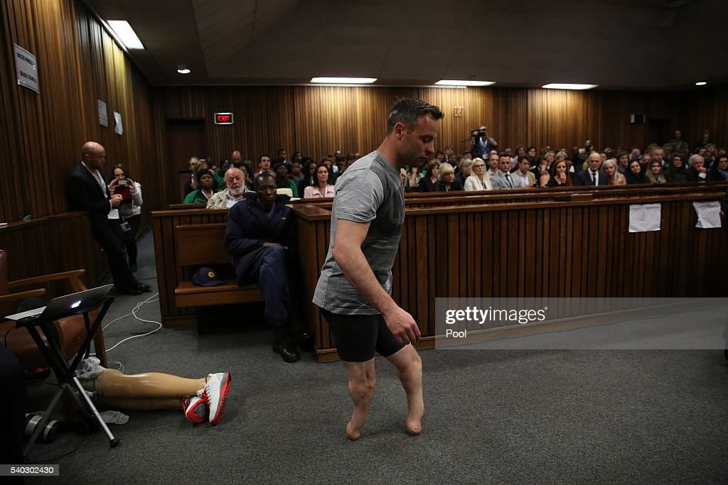 Oscar Pistorius walks across the courtroom without his prosthetic legs during the third day of Oscar's hearing for a resentence at Pretoria High...