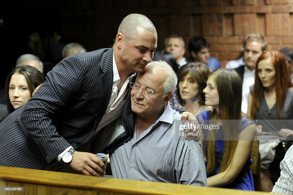 Oscar Pistorius's brother Carl Pistorius comforts their father Henk Pistorius during Oscar's bail hearing in the Pretoria Magistrate Court on...