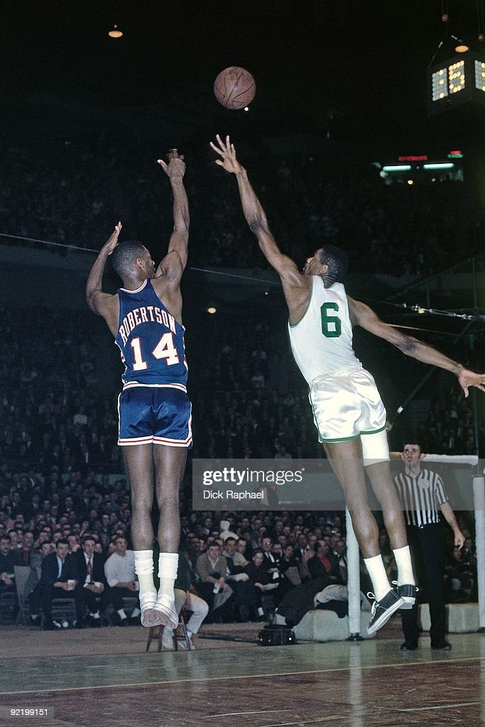 Oscar Robertson #14 of the Cincinnati Royals shoots a jump shot over Bill Russell #6 of the Boston Celtics during a game played in 1964 at the Boston Garden in Boston, Massachusetts.
