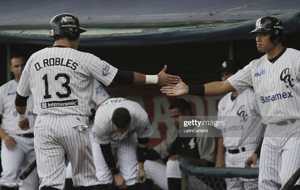 <a gi-track='captionPersonalityLinkClicked' href=/galleries/search?phrase=Oscar+Robles&family=editorial&specificpeople=240426 ng-click='$event.stopPropagation()'>Oscar Robles</a> celebrates with a teammate after scoring a run during a match between Tigres de Quintana Roo and Guerreros de Oaxaca as part of the Mexican Baseball League 2014 at Eduardo Vasconcelos Stadium on July 26, 2014 in Oaxaca, Mexico.