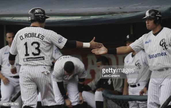 Oscar Robles celebrates with a teammate after scoring a run during a match between Tigres de Quintana Roo and Guerreros de Oaxaca as part of the...