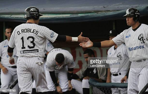 Oscar Robles celebrates with a teammate after scoring a run during a match between Tigres de Quintana Roo and Guerreros de Oaxaca as part of the...