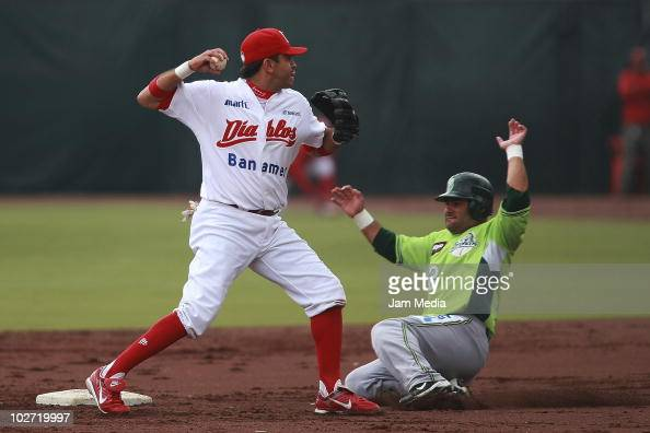 Oscar Robles of Diablos Rojos and Francisco Arias of Broncos Reynosa in action during a match as part of Mexican baseball league 2010 at the Foro Sol...