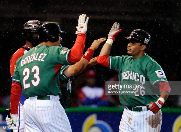 Oscar Robles of Mexico is congratulated at home plate by teammate Adrian Gonzalez after hitting a onerun home run against Cuba during the 2009 World...
