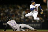 Oscar Robles of the Los Angeles Dodgers jumps out of the way of the slide from Tony Clark of the Arizona Diamondbacks as he breaks up a double play...
