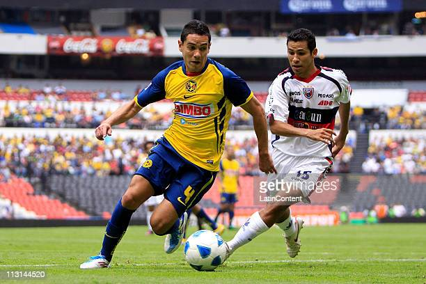 Oscar Rojas of America struggles for the ball with Arturo Munoz of Atlante during a match as part of the Clausura Tournament 2011 at Blue Stadium on...