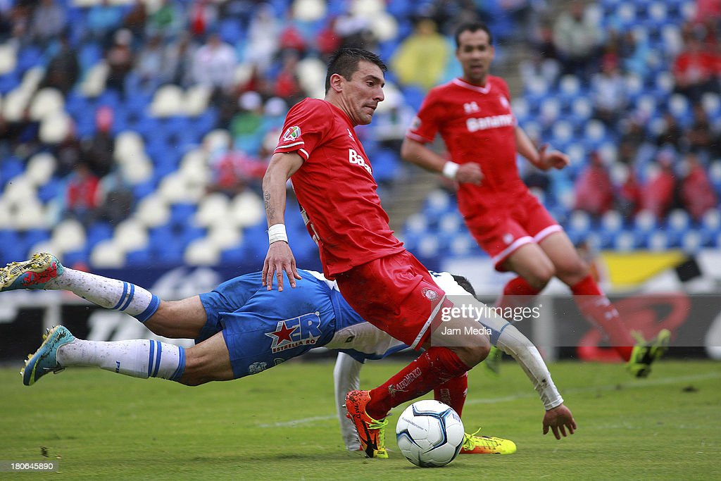 Oscar Rojas (L) of Puebla struggles for the ball with <a gi-track='captionPersonalityLinkClicked' href=/galleries/search?phrase=Edgar+Benitez&family=editorial&specificpeople=3433635 ng-click='$event.stopPropagation()'>Edgar Benitez</a> (R) of Toluca during a match as part of Apertura 2013 Liga MX at Cuauhtemoc Stadium on September 14, 2013 in Puebla, Mexico.