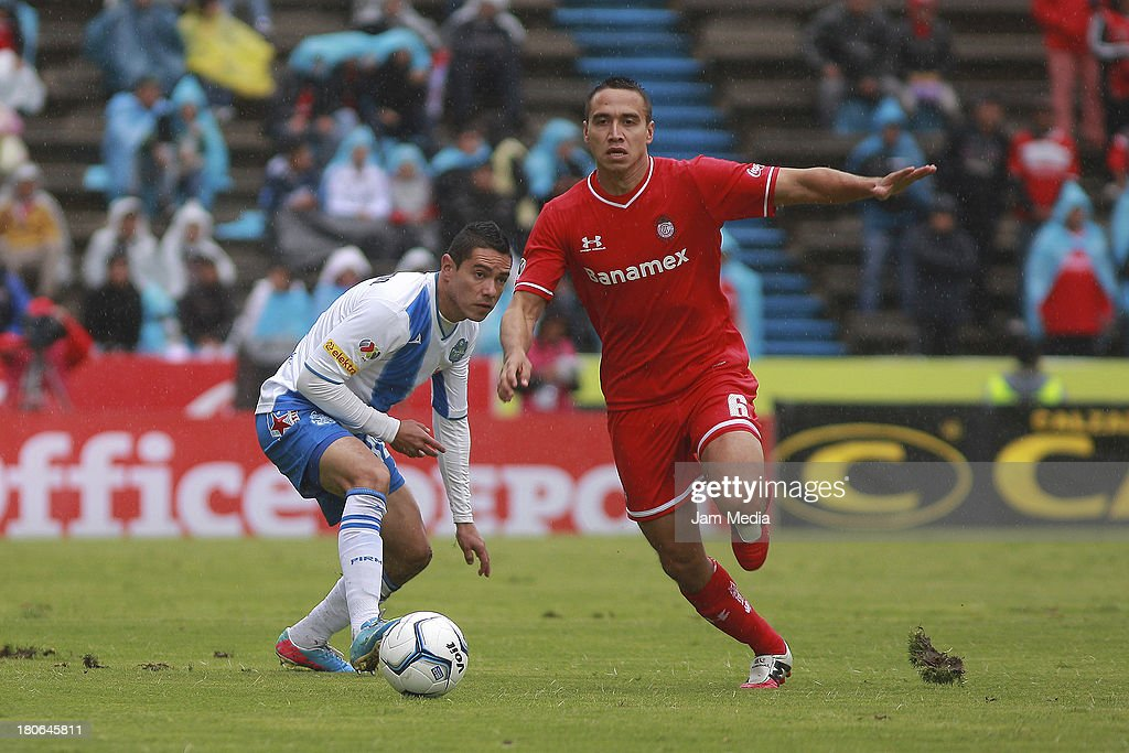 Oscar Rojas (L) of Puebla struggles for the ball with Gerardo Rodriguez (R) of Toluca during a match as part of Apertura 2013 Liga MX at Cuauhtemoc Stadium on September 14, 2013 in Puebla, Mexico.