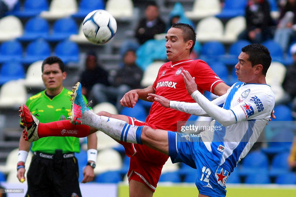 Oscar Rojas (R) of Puebla struggles for the ball with Gerardo Rodriguez (L) of Toluca during a match as part of Apertura 2013 Liga MX at Cuauhtemoc Stadium on September 14, 2013 in Puebla, Mexico.