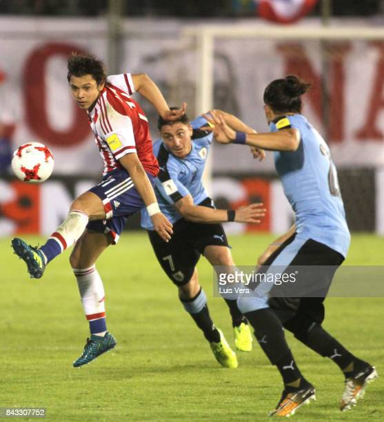 Oscar Romero of Paraguay fights for the ball with Martin Caceres and José María Gimenez of Uruguay during a match between Paraguay and Uruguay as...