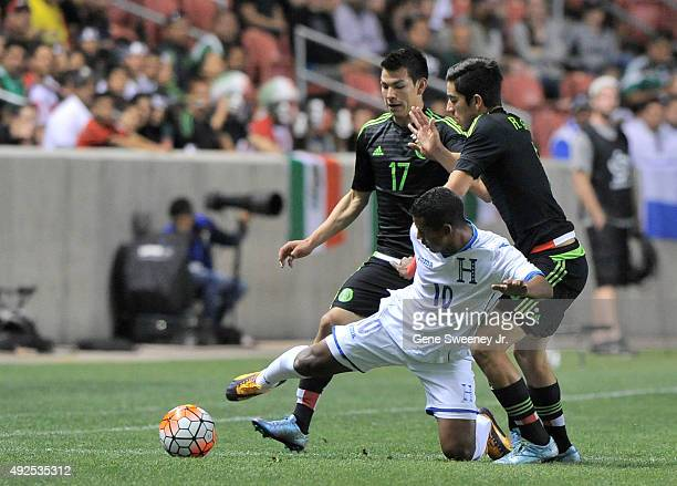 Oscar Salas of Honduras tries to keep the ball away from Hirving Lozano and Rodolfo Pizarro both of Mexico during the first half of the final...