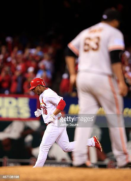 Oscar Taveras of the St Louis Cardinals rounds the bases after hitting a solo home run in the seventh inning as Jean Machi of the San Francisco...