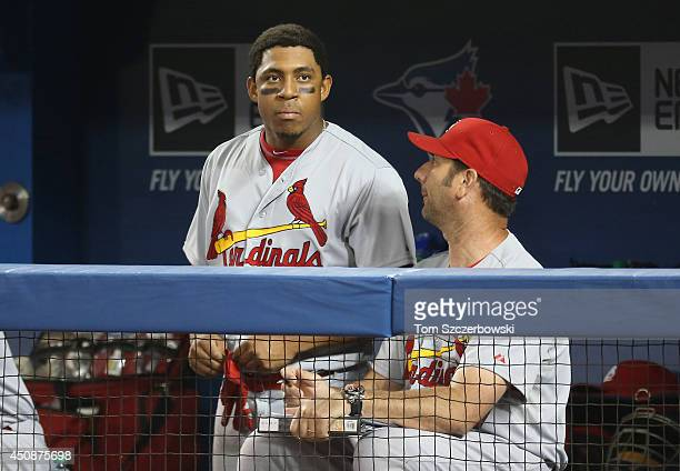 Oscar Taveras of the St Louis Cardinals talks to hitting coach John Mabry in the dugout during MLB game action against the Toronto Blue Jays on June...