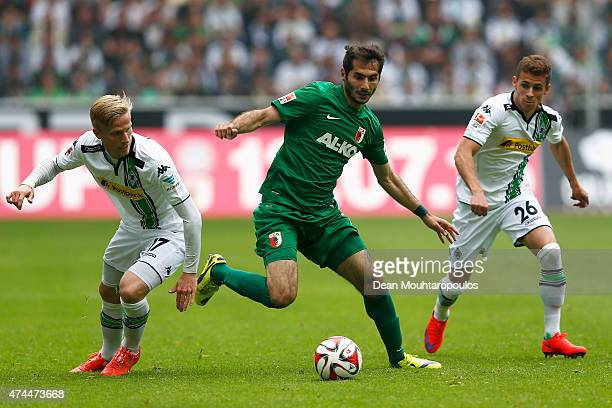 Oscar Wendt and Thorgan Hazard of Borussia Moenchengladbach chase Halil Altintop of FC Augsburg during the Bundesliga match between Borussia...