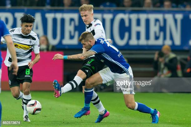 Oscar Wendt of Borussia Moenchengladbach and Guido Burgstaller of Schalke battle for the ball during the UEFA Europa League Round of 16 first leg...