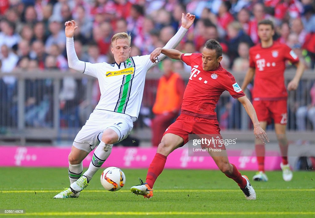 Oscar Wendt of Borussia Moenchengladbach and Rafinha of Bayern Muenchen compete for the ball during the Bundesliga match between Bayern Muenchen and Borussia Moenchengladbach at Allianz Arena on April 30, 2016 in Munich, Germany.