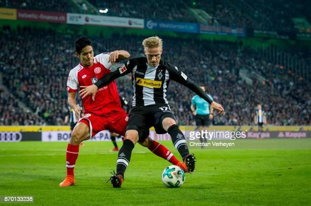 Oscar Wendt of Borussia Moenchengladbach and Yoshinori Muto of FSV Mainz 05 battle for the ball during the Bundesliga match between Borussia...