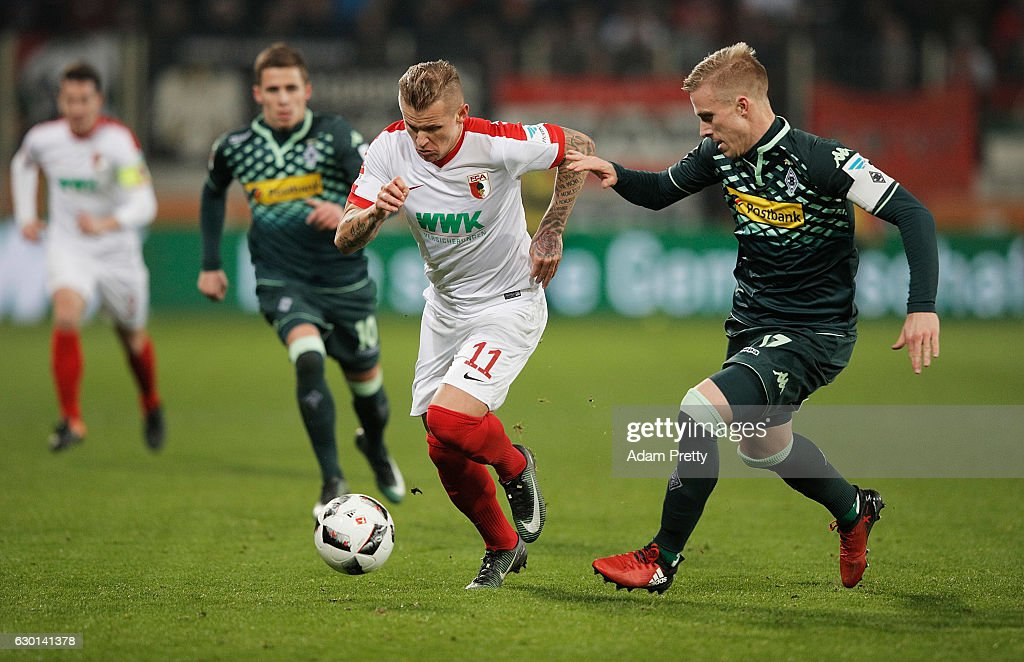Oscar Wendt of Borussia Moenchengladbach challenges Jonathan Schmid of Augsburg during the Bundesliga match between FC Augsburg and Borussia Moenchengladbach at WWK Arena on December 17, 2016 in Augsburg, Germany.