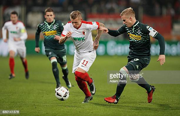 Oscar Wendt of Borussia Moenchengladbach challenges Jonathan Schmid of Augsburg during the Bundesliga match between FC Augsburg and Borussia...