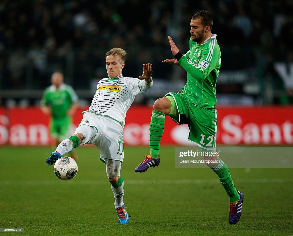Oscar Wendt of Moenchengladbach and <a gi-track='captionPersonalityLinkClicked' href=/galleries/search?phrase=Bas+Dost&family=editorial&specificpeople=7467816 ng-click='$event.stopPropagation()'>Bas Dost</a> of Wolfsburg battle for the ball during the Bundesliga match between Borussia Moenchengladbach and VfL Wolfsburg held at Borussia-Park on December 22, 2013 in Moenchengladbach, Germany.