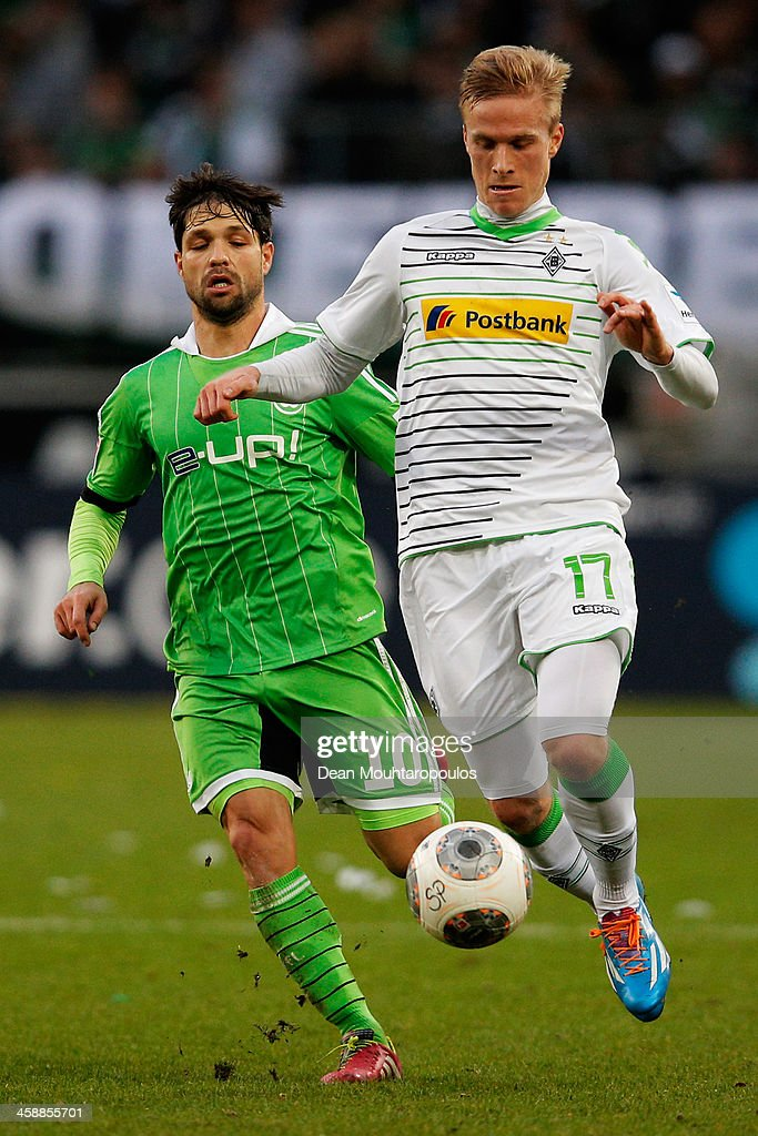 Oscar Wendt of Moenchengladbach and Diego of Wolfsburg battle for the ball during the Bundesliga match between Borussia Moenchengladbach and VfL Wolfsburg held at Borussia-Park on December 22, 2013 in Moenchengladbach, Germany.