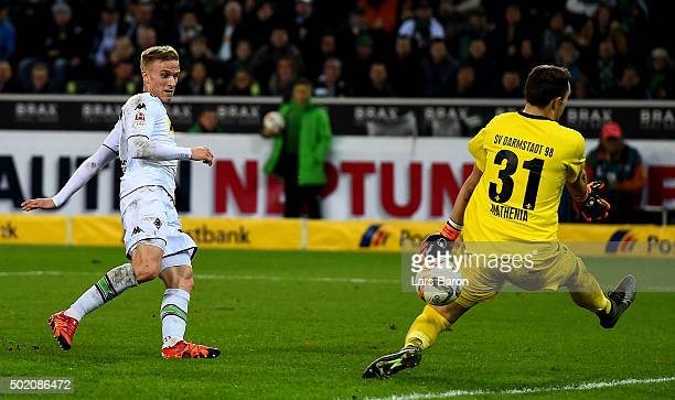 Oscar Wendt of Moenchengladbach scores his teams third goal against goalkeeper Christian Mathenia of Darmstadt during the Bundesliga match between...