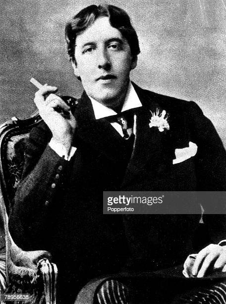 Oscar Wilde Irish playwright essayist and poet smoking a cigarette as he sits down in a chair