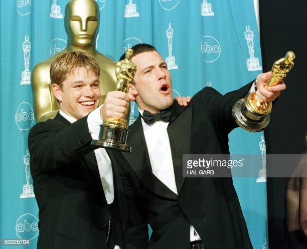 Oscar winners Matt Damon and Ben Affleck hold the awards they won for best original screenplay for the film 'Good Will Hunting' which the two wrote...