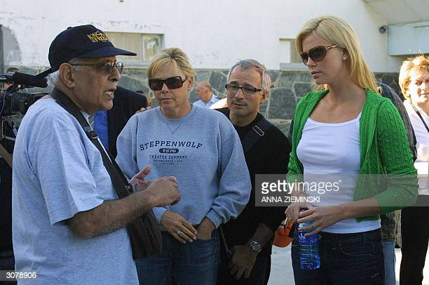 Oscar winning actress Charlize Theron and her mother Gerda listen to former political prisoner Ahmed Kathrada in the courtyard of the cell block...