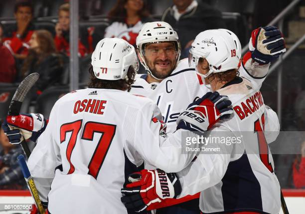 TJ Oshie Alex Ovechkin and Nicklas Backstrom of the Washington Capitals celebrate a third period goal by Backstrom against the New Jersey Devils at...