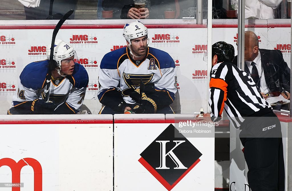 T.J. Oshie #74 and Barret Jackman #5 of the St. Louis Blues receive instruction from referee Kyle Rehman #37 in the penalty box against the Anaheim Ducks on March 10, 2013 at Honda Center in Anaheim, California.